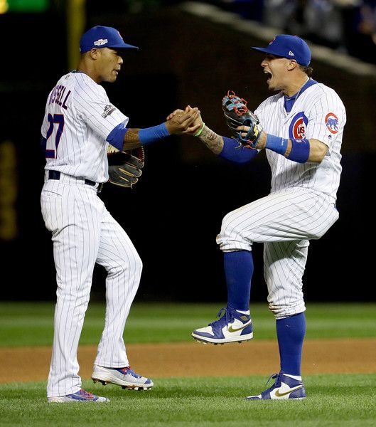 Addison Russell #27 and Javier Baez #9 of the Chicago Cubs celebrate after beating the San Francisco Giants1-0 at Wrigley Field on October 7, 2016 in Chicago, Illinois.