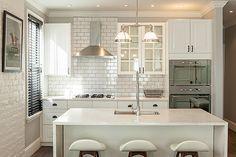 Cozinha pequena, branca e clássica.