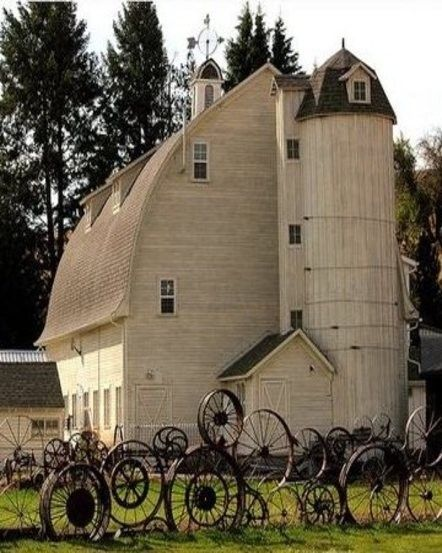Old White Barn...rustic fence made from metal wagon wheels.