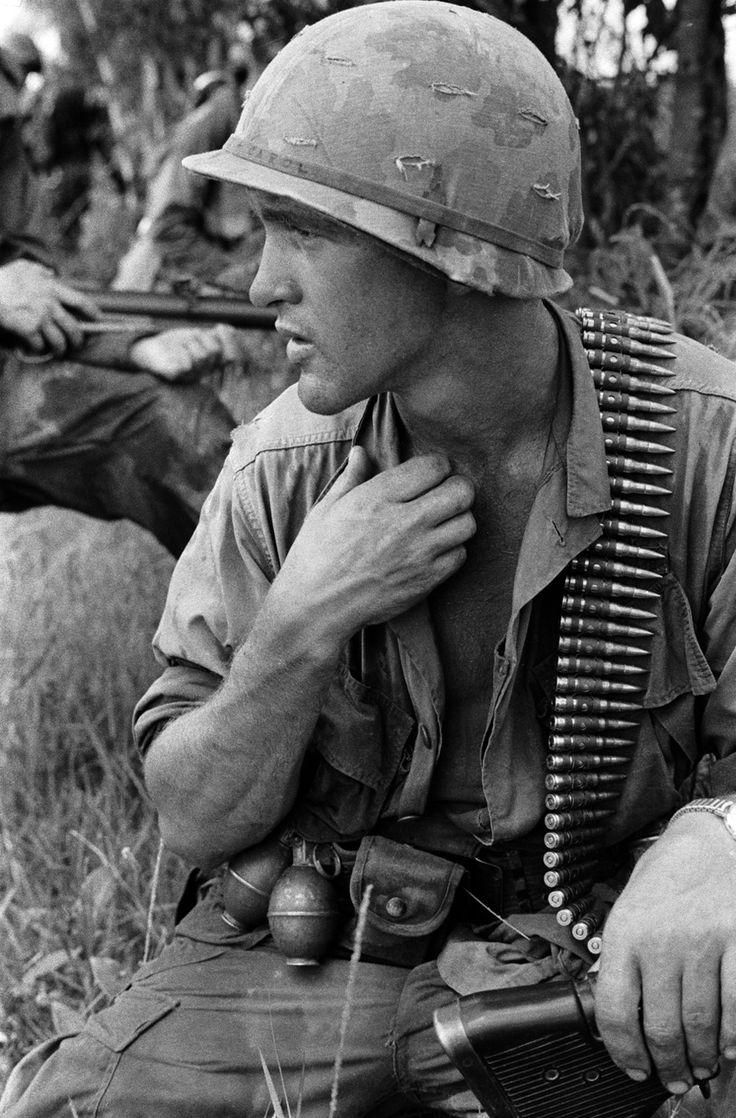 Um operador de M60 pausa por um momento sob a pesada carga de munição de metralhadora. Os membros da unidade foram todos obrigados a ter algum tipo de munição ou acessórios, incluindo cartucheiras de balas pesadas. Nome, data e local desconhecido.