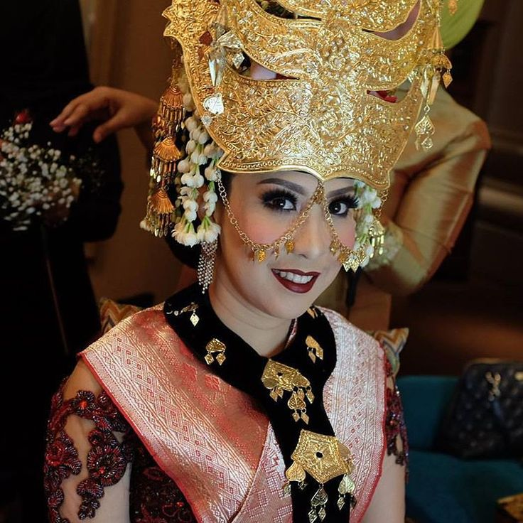 """In Mandailing culture, the wedding attire is dominated by combination shades of red, gold and black. The bride will also wear a gold colored headpiece…"""