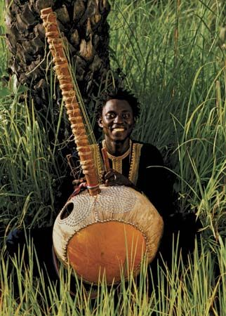 Gambian musician playing the kora, a complex stringed instrument.