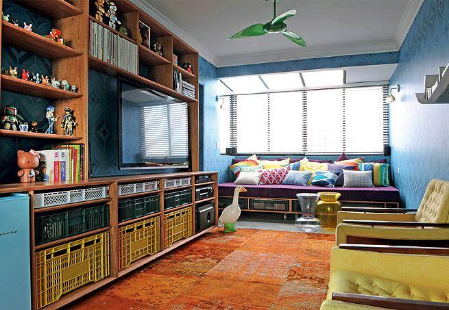 En la zona ancha, panel de madera Cumaru se eleva desde el suelo hasta la pared.  La instalación de cañerías da contraste inmediata.  Gris gana poder pinches con tonos de rojo en los cojines y las impresiones en geometrías alfombra de carbón del diseño