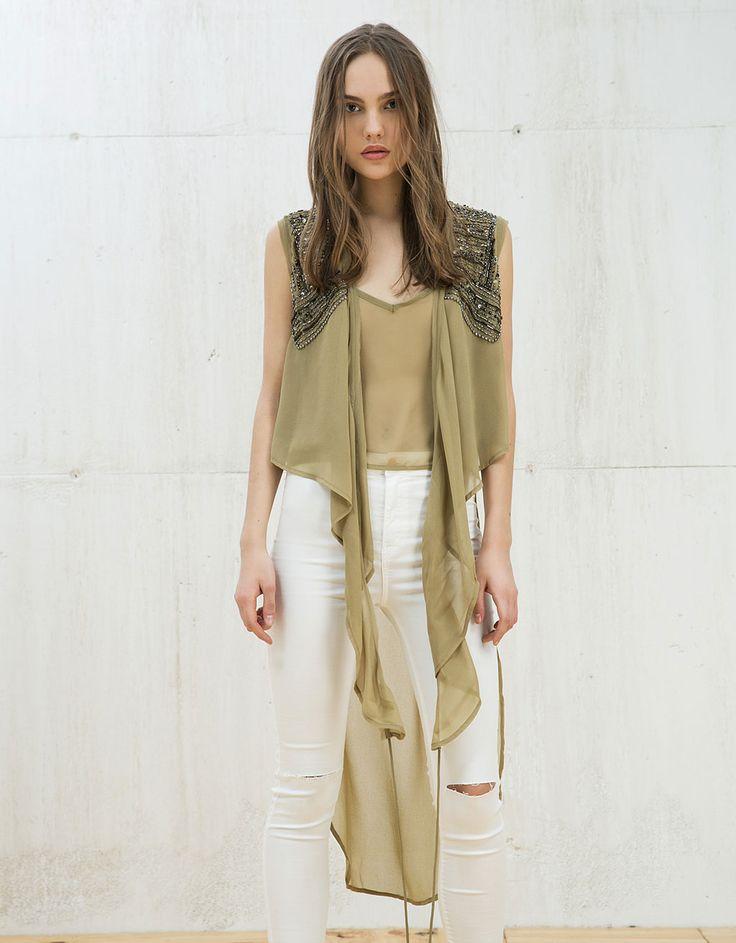 Blusa asimétrica con nudo y bordados. Descubre ésta y muchas otras prendas en Bershka con nuevos productos cada semana