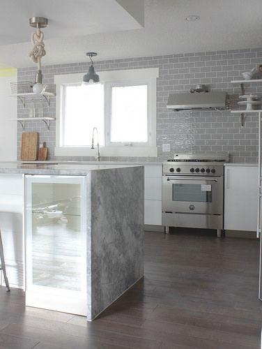 Laurier house. Super White Dolomite on island. Back counters solid white Quartz.  Grey backsplash CLGP 36 Classical 3x6 Grigio Perla.   Bertazzoni range.