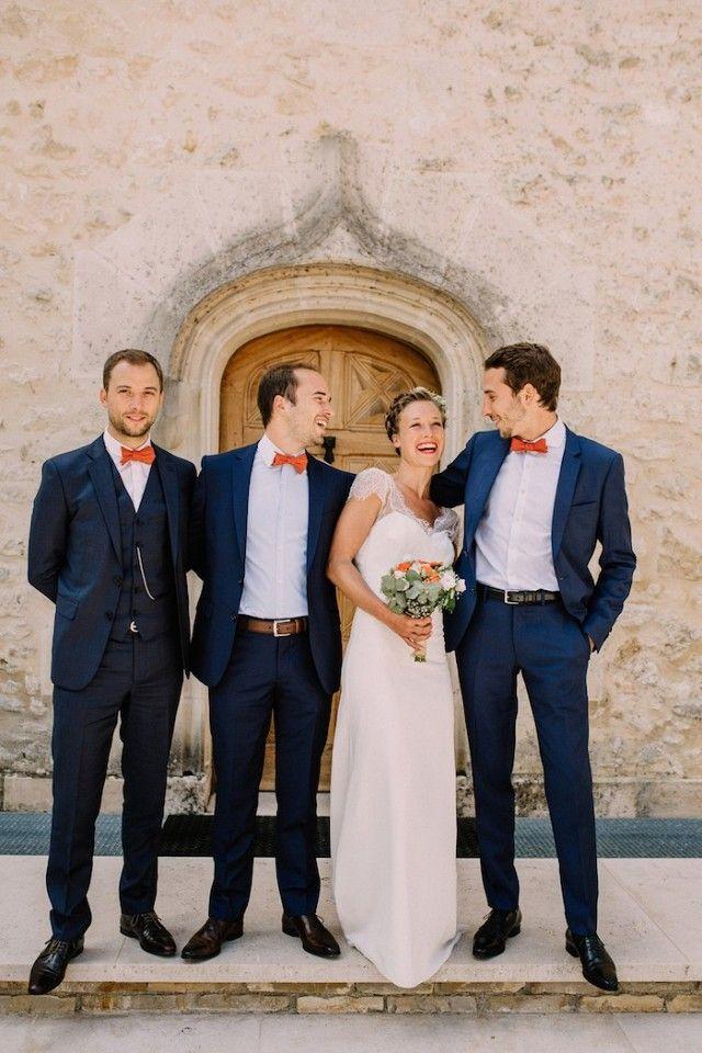 Groomsmen in dark blue tuxedos and orange bowties, bride in lace wedding dress