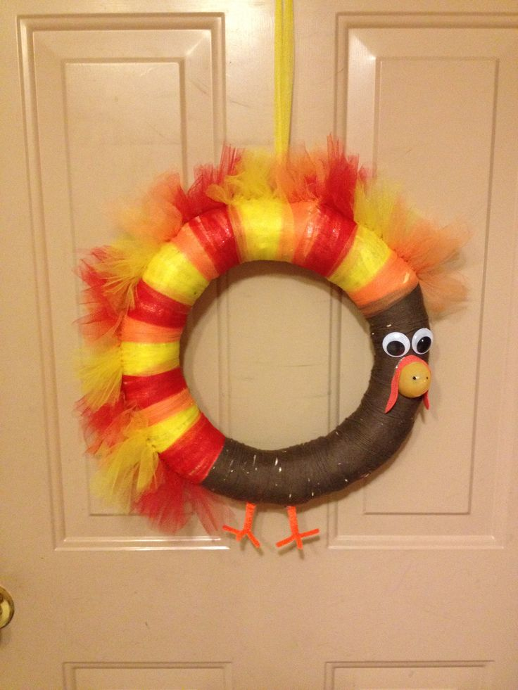 """Turkey wreath for thanksgiving. Made with tulle, brown yarn, pipe cleaners, 1/2 plastic Easter egg, foam, googly eyes, and a 14"""" straw circle."""
