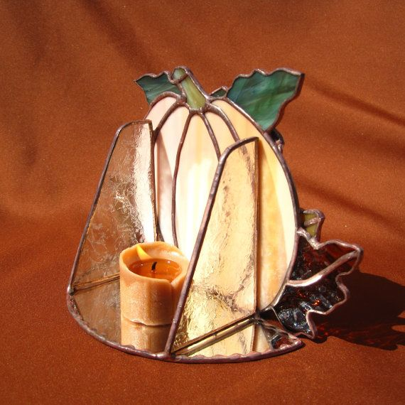 This is a candle holder that can be used throughout the fall season. It stands alone and is designed to hold a small candle behind the pumpkin. I created this candle holder of 34 hand cut pieces of stained glass. Most of the glass in this piece was cut with a glass band saw. The main