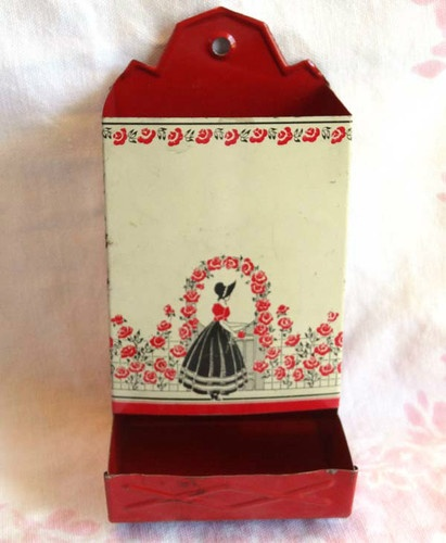 """On Ebay: This is a charming """"cottage chic"""" antique tin lithograph match safe kitchen wall holder. The design is black and red on cream, and depicts a lady with a bonnet in a rose garden."""