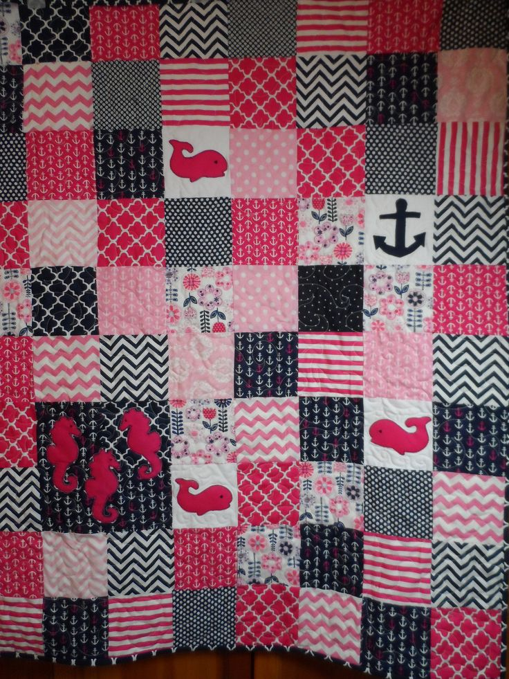 Nautical baby girl quilt navy and bright pink. Handmade nautical blanket with anchors, whales, seahorses. This is a bright pink and dark navy quilt,with nautical prints and a pretty coordinating floral print to add a feminine touch. Quite pretty.  Quilt country original design. Special features: appliqued seahorses, whales and 1 anchor.  Make this piece a showcase in your babys nursery, one that she will love. Made to last, the cotton fabric and batting, along with the meandering quilting…
