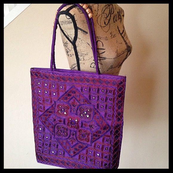 """Indian embroidered purple tote bag NWOT Beautiful tote bag, embroidered in lovely shades of purple! Also features beads on the handles and coin sized mirrors on the outside of the front. The back is plain, with no embellishments, just the purple material. This was a boutique gift from a friend who had been traveling the world; never used. Measures approximately 16"""" tall, 15.5"""" wide and about 3"""" deep. Measurements do not include the handles. Bags Totes"""