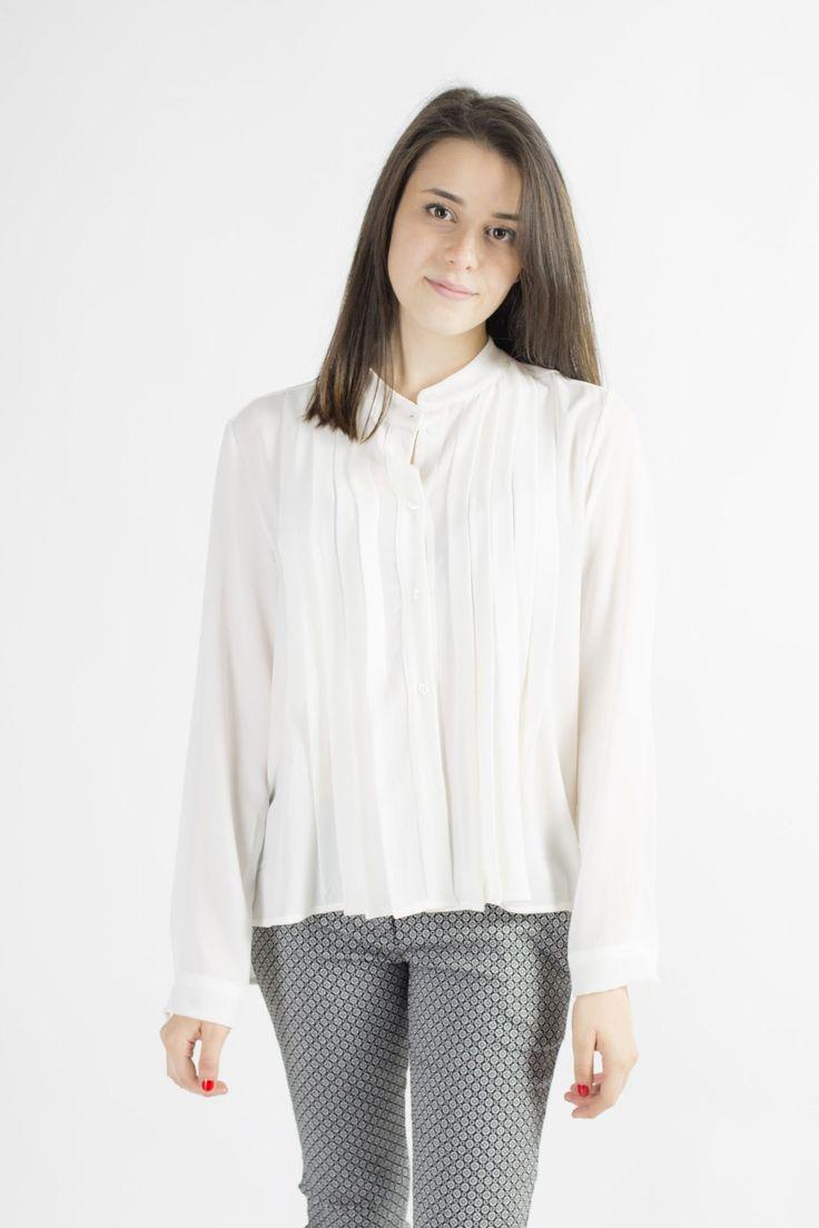 Camicia tinta unita a manica lunga con collo alla coreana allacciata con bottoni in tinta. Dal collo e dalla spalla scendono per tutta la lunghezza della camicia delle pieghine.