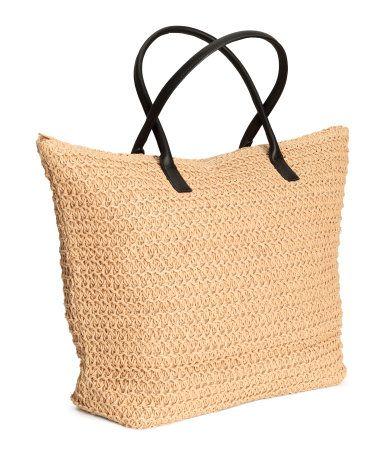 Naturel. Een zachte strooien tas met twee hengsels van imitatieleer en een ritssluiting boven. De tas is gevoerd en heeft twee binnenvakken. Afmetingen