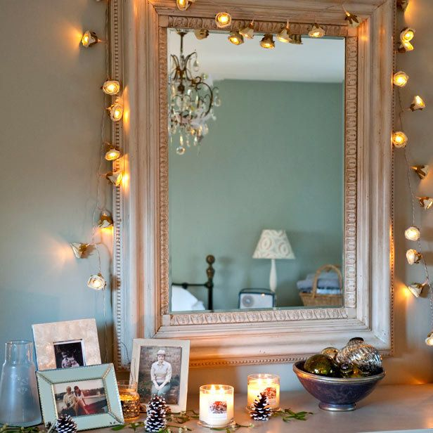 For a Hollywood Glam vanity, add inexpensive string lighting around a large mirror over a tabletop or desk. (Of course, the chandelier in the background doesn't hurt!)