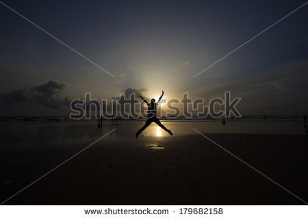 Jump of Success.Silhouette at sunset showing happiness. - stock photo