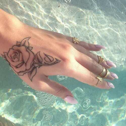 small rose tattoo on hand