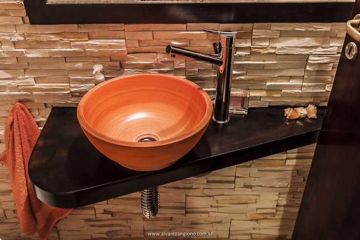 En este pequeño baño de bajo de una escalera, pero muy integrado a los espacios comunes de la casa, por ende muy visible, quise poner hincapié en lograr un lugar sofisticado y divertido, dándole a este espacio la calidez de la piedra y la madera, utilizando solo un impacto de color, puesto en la bacha naranja. Y de eso modo, con pocos elementos lograr el objetivo, sofisticación, diseño y color. El gran espejo logra desaparecer las pequeñas dimensiones del lugar.