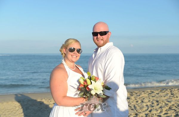 Beach bride with sunglasses and wedding flower bouquet on the Ocean City, MD Clarion hotel beach: https://www.roxbeachweddings.com/