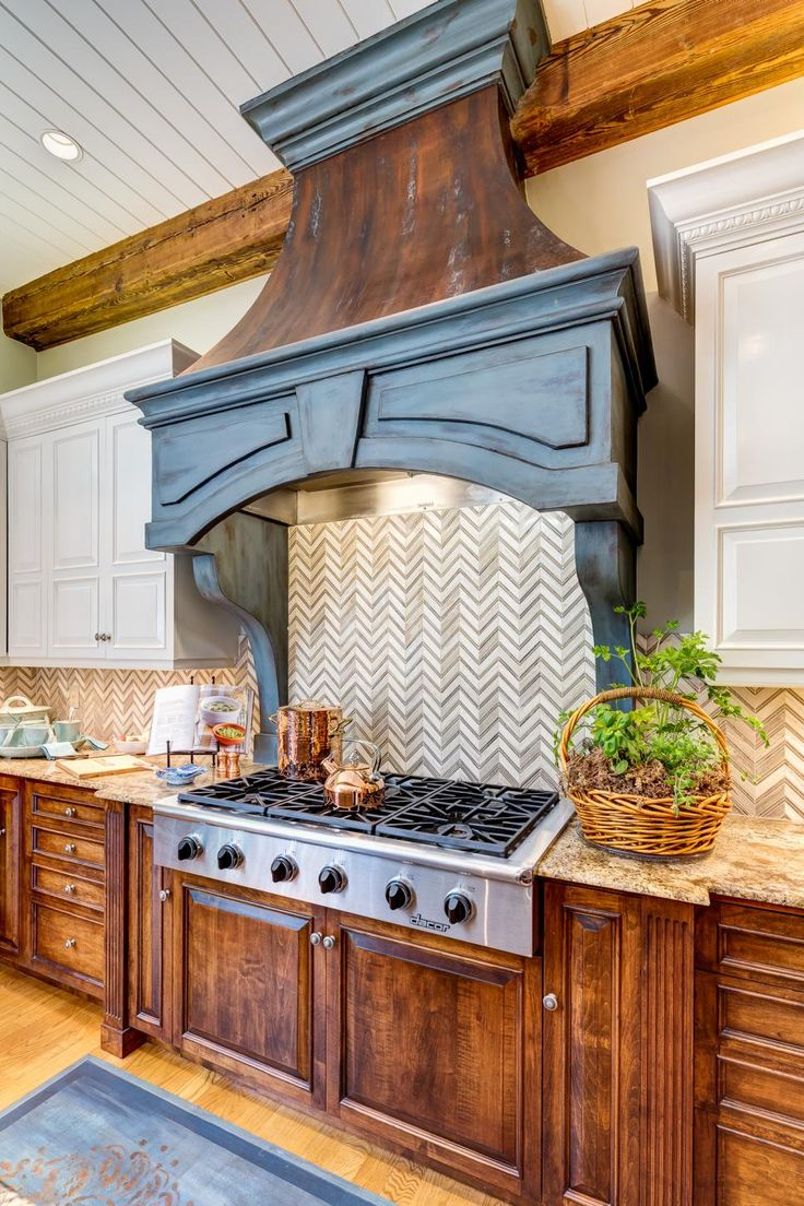 honed marble makes a chevron pattern backsplash behind the gas stove the faux bronze range