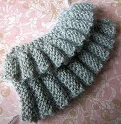 Layers of short-row ruffles. - Cast on 9 sts. Row 1: Knit. Row 2: P6 and turn, k6. Row 3: P6, k3. Row 4: K3, p6. Row 5: K6 and turn, p6. Row 6: Knit.- Repeat these 6 rows for your desired length.