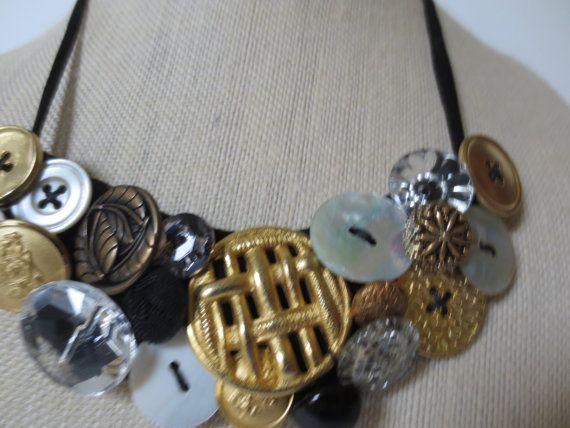 Este collar es una combinación de botones contemporánea y vintage. Tono oro y plateado, madre o perlas, Strass y botones negros. Cuerda doble de poliéster negro con cierre de cordón. Sentía respaldado. Botón de oro tejido en el centro. Los botones son mano cosida y anudadas individualmente. Hipoalergénico, no metal tocando su piel. Diseñé este porque tengo sensibilidad de la piel. Collar es de 5-1/2 de ancho, 20 de largo y viene con extensor de 3. También viene con una bolsa de triple a ...