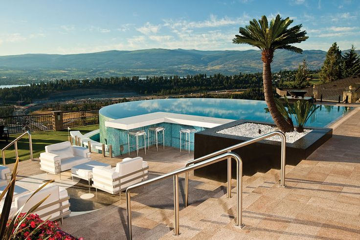 Elevated infinity pool with mountain view and palm trees for Pool design kelowna