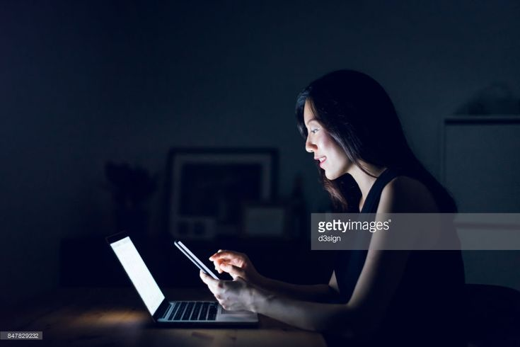 Stock Photo : Busy young woman text messaging on smartphone while working on laptop till late in home office