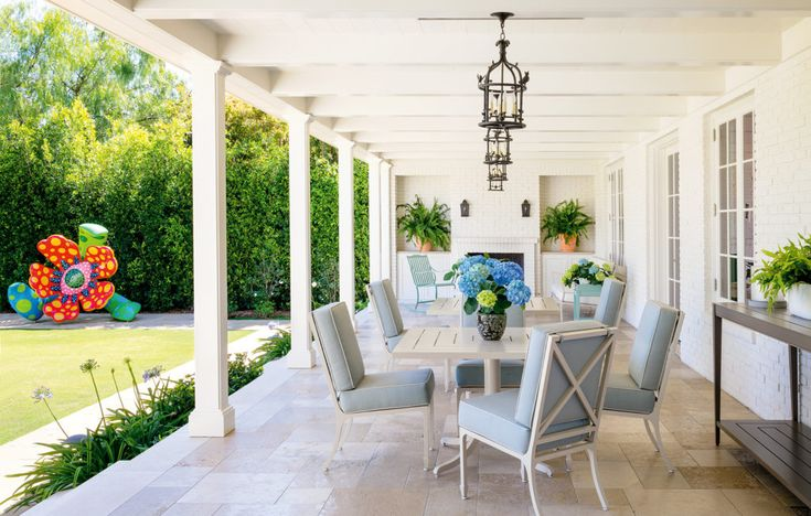 On the covered terrace, Carole Gratale lanterns are installed above McKinnon and Harris tables and chairs, the latter upholstered in a Perennials fabric. - photo: Trevor Tondro