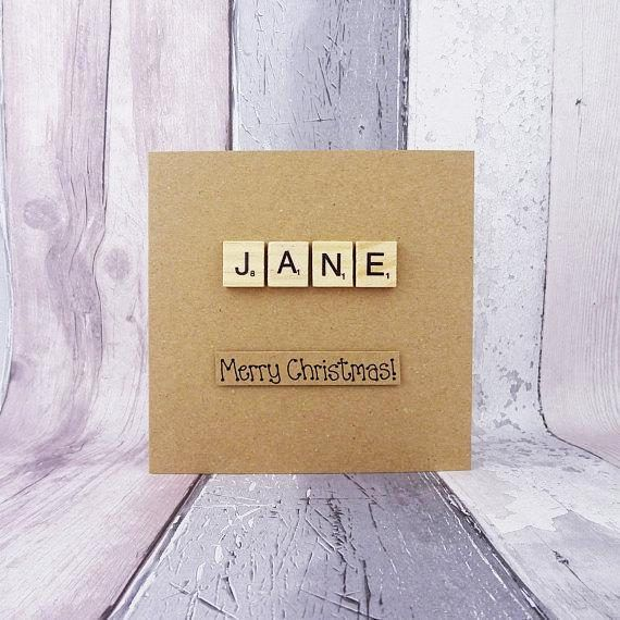This handmade Christmas card features Scrabble alphabet tiles spelling out the name of your choice.  The sentiment on this handmade Christmas Scrabble tile card is added with 3D foam and reads: Merry Christmas! Or you can pick another message from the drop-down menu or even create your