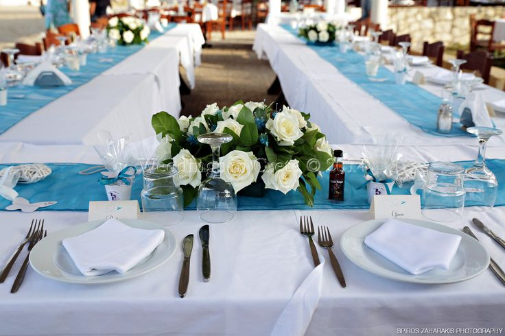Weddings in Crete - Flower arrangement of white roses and greenery on turquoise table runner - by Weddings in Crete