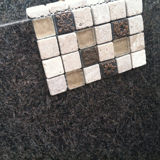 coffee brown granite countertop coupled with a mosaic tile surround with combo brings together the white from cabinets and