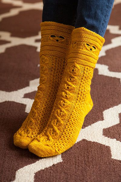 Knit a pair of Busy Bees socks, featuring a cable honeycomb design and bee motif around the cuff. Pattern available at www.knitpicks.com