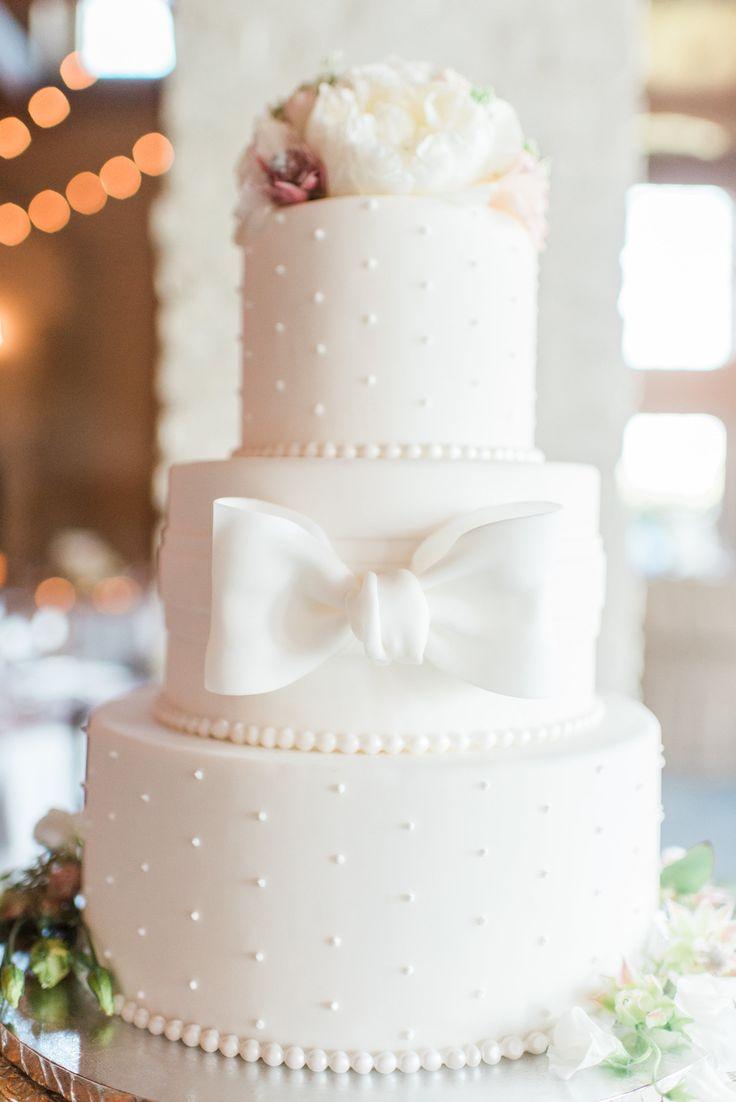 White wedding cake, large fondant bow, polka dots, white floral cake topper // Jillian Michelle Photography