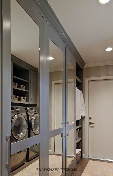 Laundry room with floor to ceiling mirrored cabinets by Bradshaw Designs. Via Decor Pad.