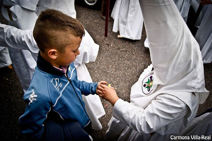 A little nazareno from San Gonzalo Brotherhood giving a candy to other child. It's a tradition in Seville that children ask for wax or candies to the nazarenos. Semana Santa 2012, Hermandad de San Gonzalo (Sevilla) Lunes Santo. Photo: José Antonio Carmona Villa-Real