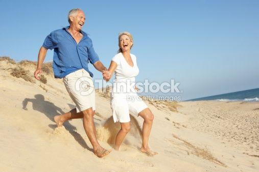 Stock Photo : Senior Couple Enjoying Beach Holiday Running Down Sand Dune