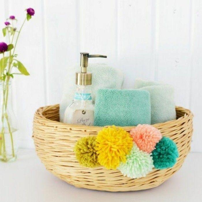 pompon en laine, panier en paille, savon liquide, serviettes propres