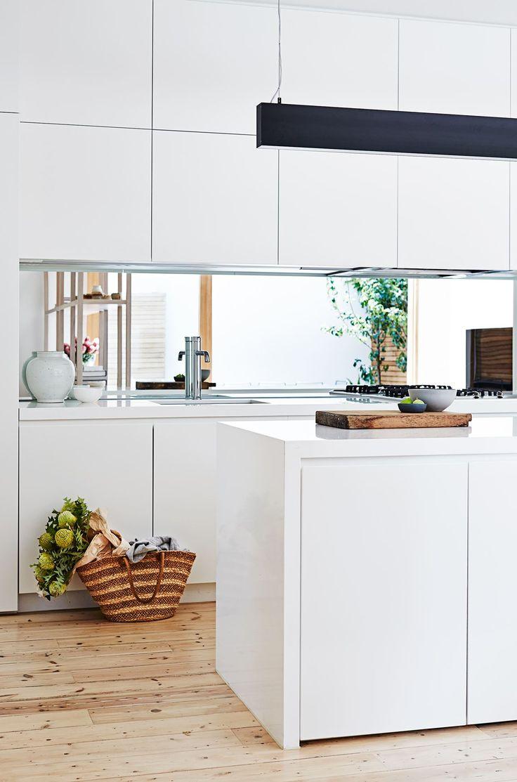 Kitchen: matt white handleless cabinets, mirror splashback, long black pendant light, storage in island
