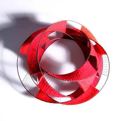 2010  David Poston. Bangle of welded stainless steel wire, tapestry woven red cottons