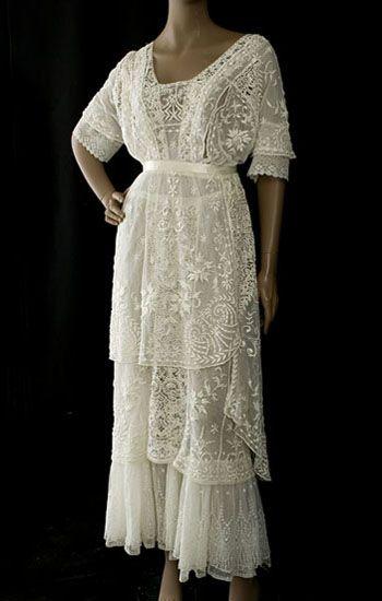 bordada a mano tul vestido de té, c.1912. Las tres capas de la falda en el diseño asimétrico ingenioso le dan un encanto digno a la novia feliz. Las dos capas exteriores son bordados a mano con motivos florales de la puntada de raso acolchado levantó con detalles de ojal
