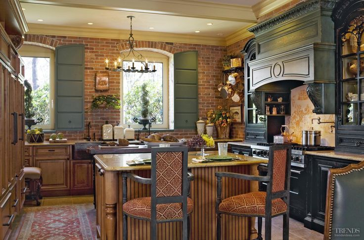 Brickwork, varied cabinetry and rich tones all give this kitchen an inviting, rustic appeal. Appliances are set on the inner side of the islands or integrated to preserve the rural look. Copper faucets and a farmhouse sink add to the charm.
