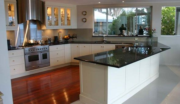Black granite benchtops with white shaker cabinets. Pretty skirting board!