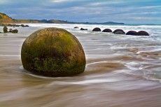 Moeraki Boulders, Koekohe Beach, Otago, New Zealand- unusually large and spherical boulders, scattered within a stretch of beach protected in a scientific reserve. The erosion by wave action of mudstone, comprising local bedrock and landslides, frequently exposes embedded isolated boulders. Local Māori legends explained the boulders as the remains of eel baskets, calabashes, and kumara washed ashore from the wreck of Arai-te-uru, a large sailing canoe.