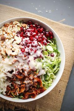 Chopped Brussels Sprout Salad - pomegranate, almonds, shaved brussels sprouts, bacon, Pecorino Romano cheese, and homemade shallot dressing!...