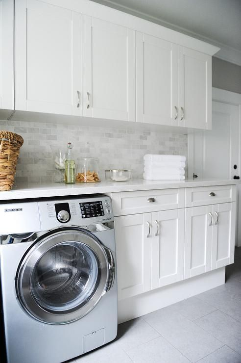 Gray laundry room features white shaker cabinets paired with white quartz countertops and a mini marble tile backsplash.