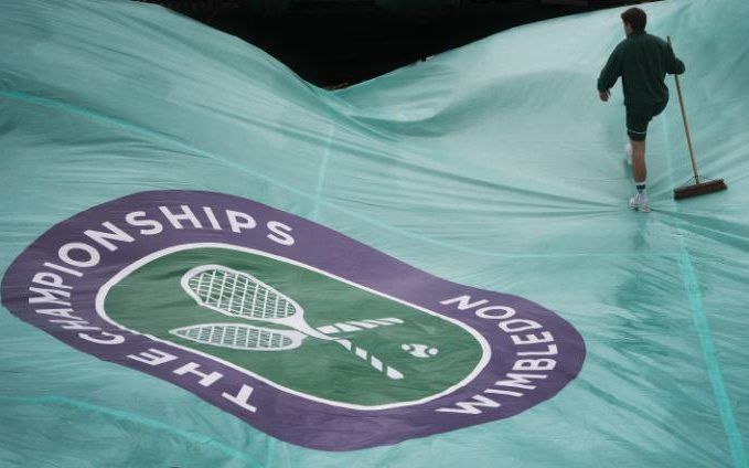 Ground staff attend to rain covers after another day at Wimbledon 2016