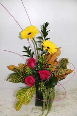 Gerbera daisies, roses, hypericum berries and amaranthus with tropical leaves.