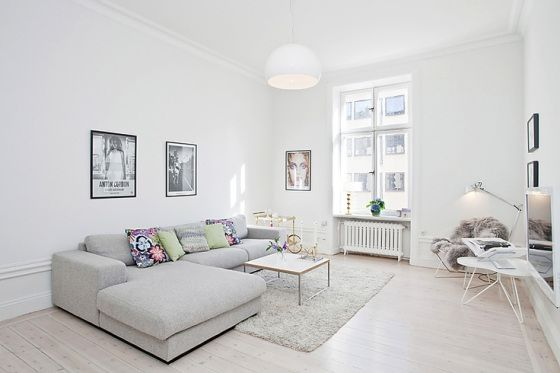 Neutral room. Light grey cream lounge, white washed floor boards and white coffee table with rug.