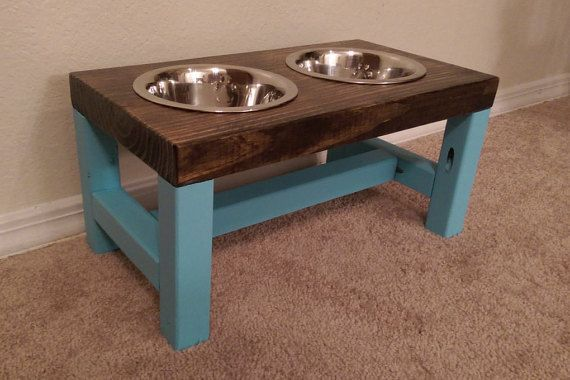 *** Farmhouse Style Dog Bowl Feeder ***  This farmhouse style dog bowl feeder is a doggie version of a classic farmhouse table! This feeder has painted turquoise legs. This item is ideal for a medium sized dog (ex: britney spaniel, bulldog, shetland sheepdog). * * * Product Details * * *  - Dimensions: L: 17 in. W: 9 1/4 in. H: 8 1/2 in. - Comes with 2, 1 quart stainless steel dog bowls - Stained wood sealed with several layers of protective coating - Painted legs in light turquoise...