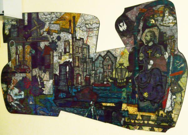 St. Bernulfius van Utrecht ~ Bernulfus als patroon van (kerkelijke) kunst met passer en schetsboek. Van links boven daalt een duif (symbool van de Heilige Geest) op hem neer.  Rechts boven een kerkje (verwijzing naar zijn bisschopszetel te Utrecht); aan zijn linkervoet het wapen van Utrecht (rood-wit) Hij kijkt vanuit de middeleeuwen naar het stadse bedrijf van de moderne tijd. Afgebeeld als patroon van de toenmalige ambachtsschool. 1964, Adr. v.d. Plas, geplakt glas. Nederland, Rijswijk…